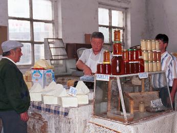Prodejce medu a domácích sýrů v kryté tržnici ve městě Krujä