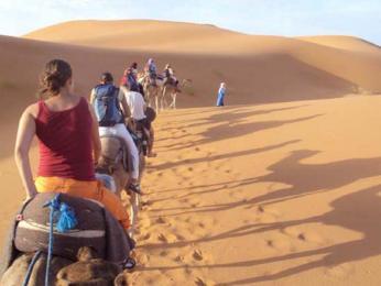 Pouštní karavana vyrážející na noc do pouště