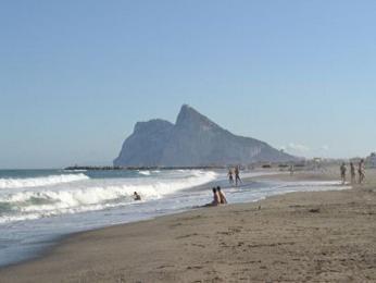 Písečná pláž se skálou Gibraltar vpozadí