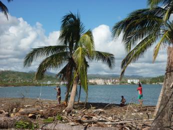 Děti hrající si na pláži vBaracoa mezi polámanými palmami