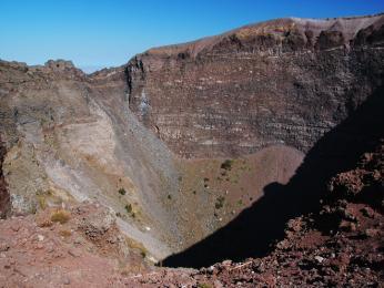 Pohled přes dřevěné zábradlí dolů do kráteru Vesuvu