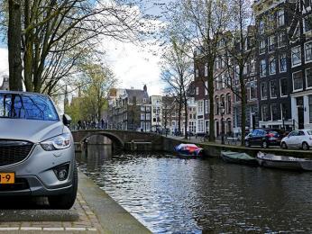 Zaparkovat auto vedle kanálu bez zábradlí vcentru Amsterdamu je umění