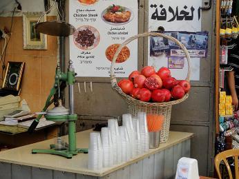 Stánek sdžusem zčerstvých granátových jablek a pomerančů