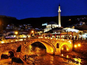 Noční Prizren sosvětleným kamenným mostem amešitou