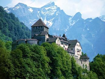Vaduzský hrad stojí na zalesněném kopci svýhledem na štíty hor