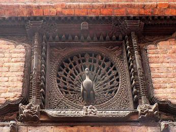 Detailně vyřezávaná okna adřevěné sošky na chrámech vBhaktapuru