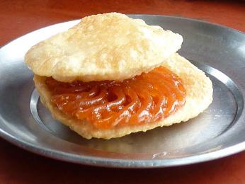 Nepálská snídaně, smažená placka puri sosmaženou sladkou mřížkou jalebi