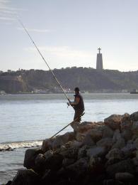 Rybář čeká vdeltě řeky Tejo na svůj úlovek