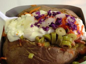 Oblíbené pouliční jídlo je kartoška kroška, brambora ve slupce rozkrojená vejpůl arůzně plněná