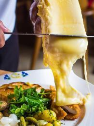 Sýr raclette se servíruje postupným seškrabáváním horní roztavené vrstvy