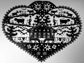 Scherenschnitte, černé siluety švýcarské přírody a zvířat na světlém pozadí