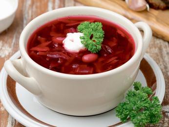 Sytě červená polévka boršč zčervené řepy zdobená smetanou