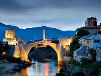 Večerní Mostar sosvětleným mostem, strážní věží aminaretem vpozadí