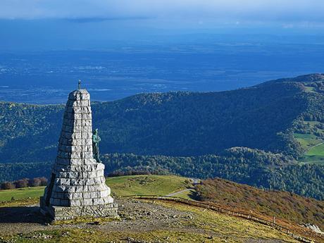 Mohyla shlížející na zalesněné zaoblené vršky pohoří Vogézy